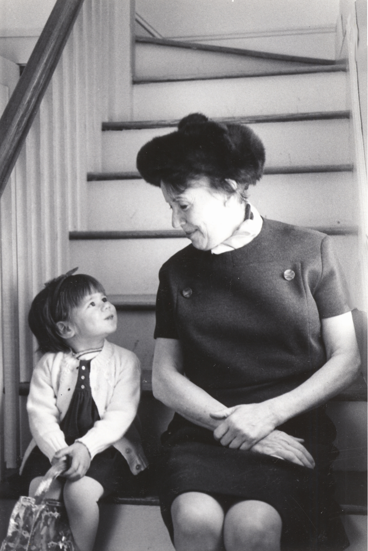 A small child sits next to her grandmother on the stairs in an old black and white photo.
