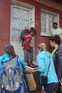 From left, students Rachel Berman and Keely O'Keefe and faculty member Alisha Farris weigh children in Madagascar as part of a summer nutrition project. Photo courtesy of Hailey Boone.