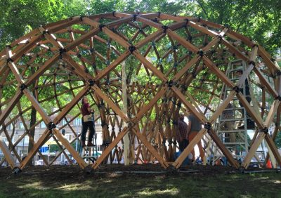 A team works to assemble the Lo-Fab Pavilion on the Rose Kennedy Greenway in Boston.