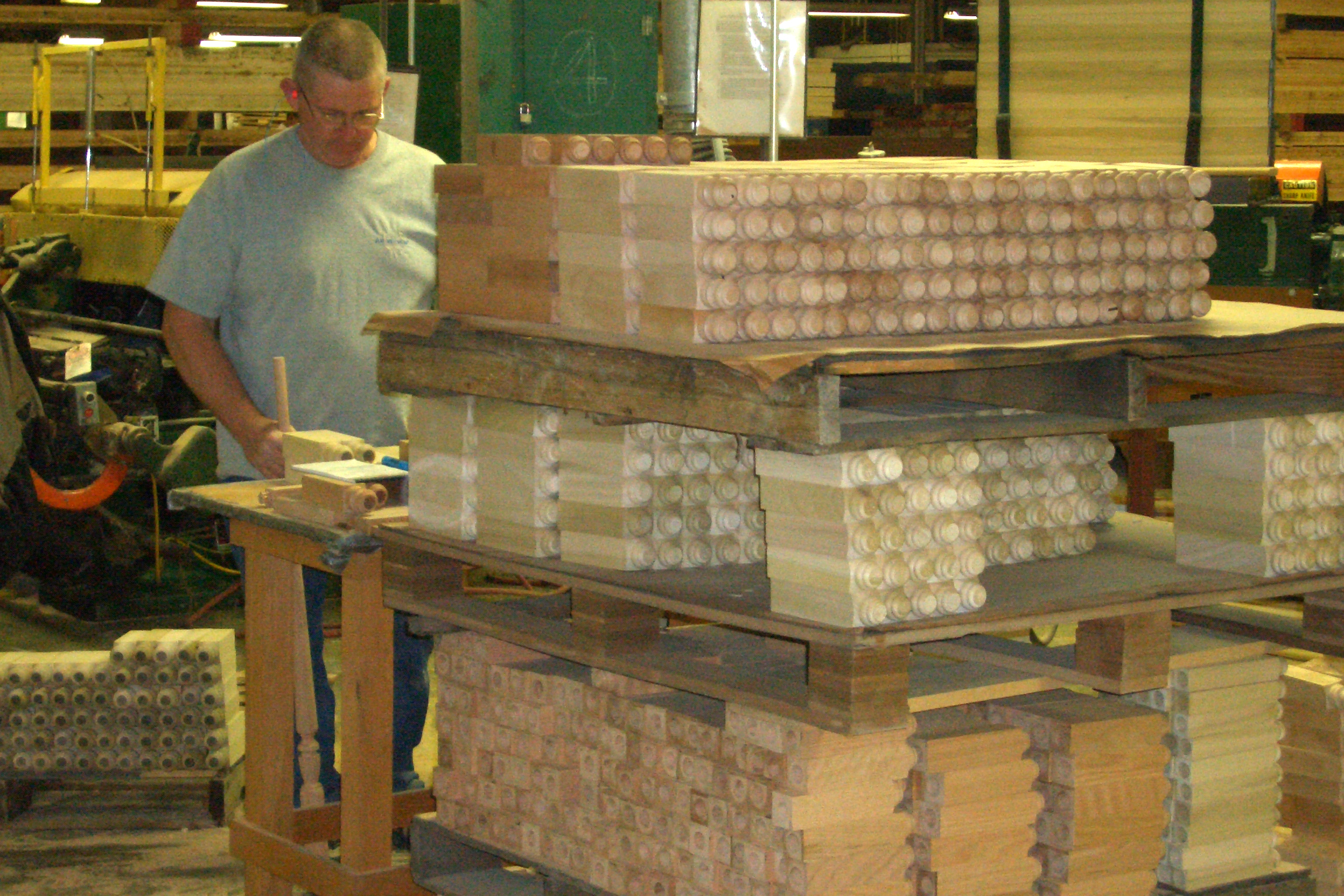 A man stands behind a pallet of wooden stair parts in a factory.