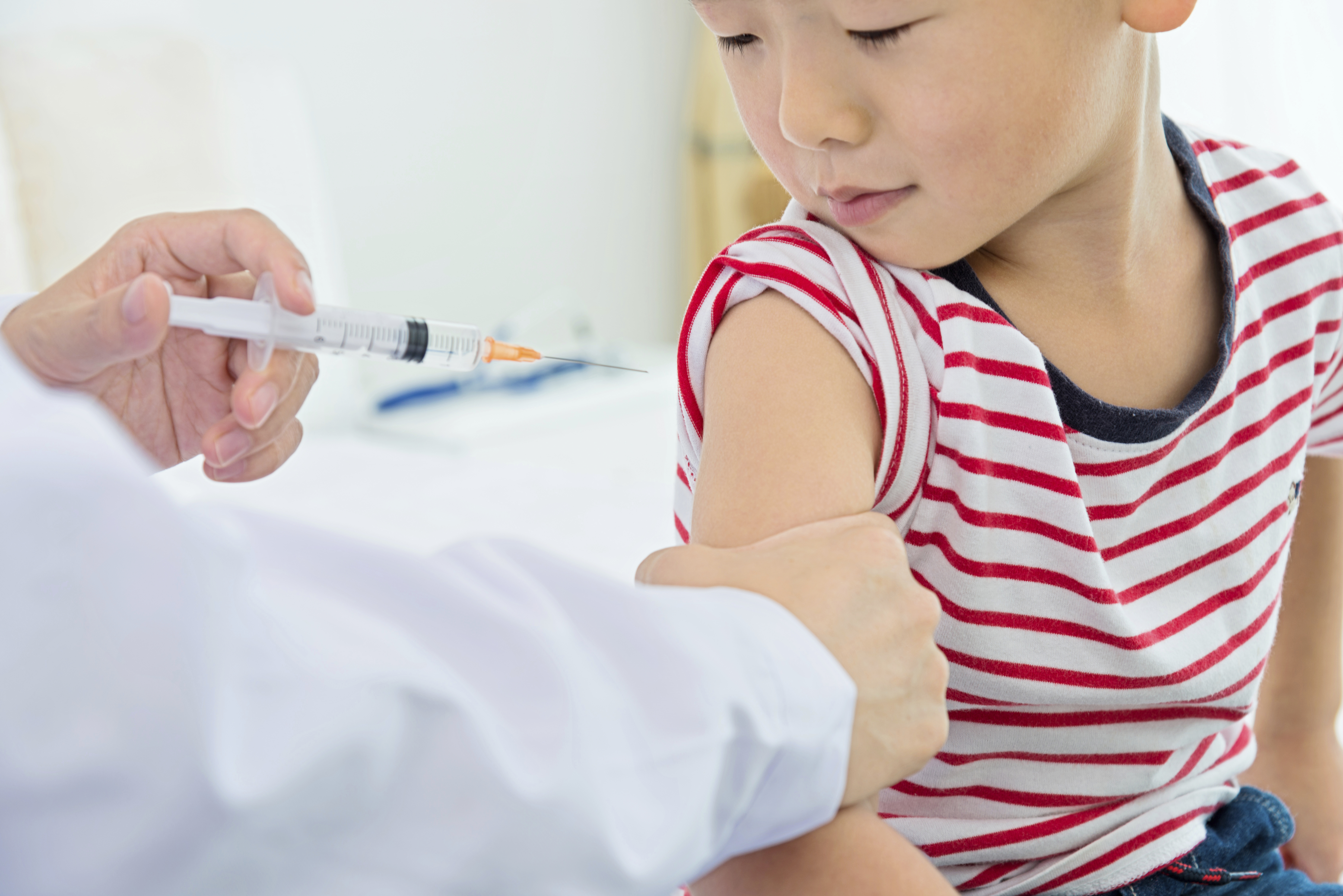 A young boy receives his vaccination with equanimity.