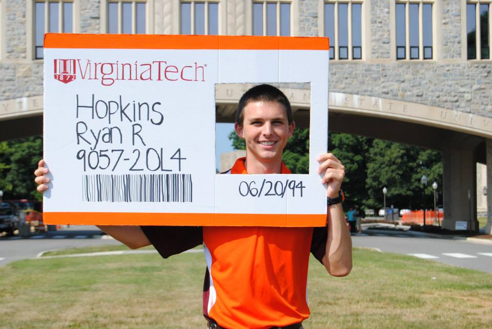 Ryan Hopkins holds a larger-than-life cardboard Hokie Passport on Virginia Tech's campus