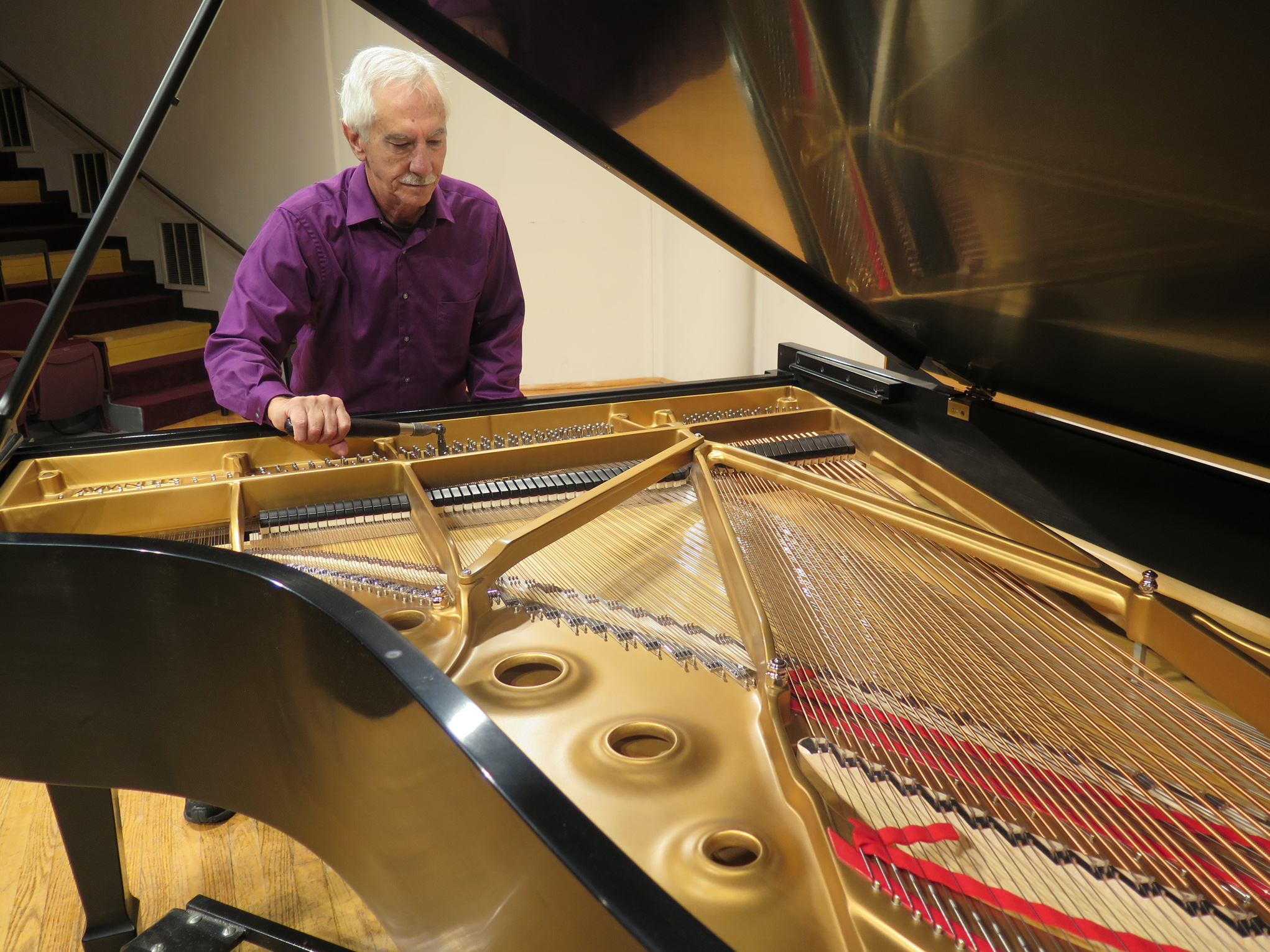 Piano technician tuning the new Steinway grand piano
