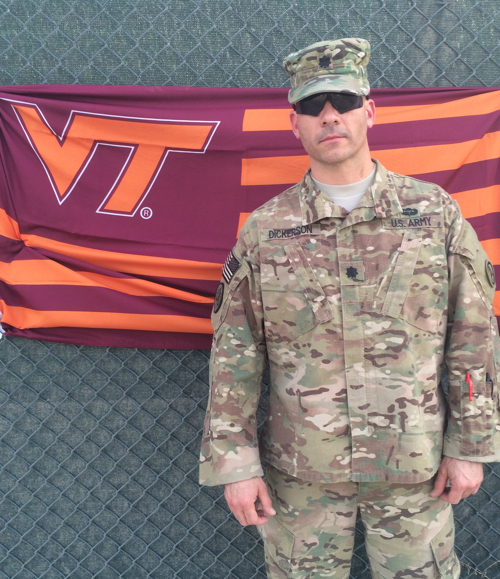 Lt. Col. Kelly Dickerson, U.S. Army, Virginia Tech Corps of Cadets Class of 1995 in front of a VT flag.