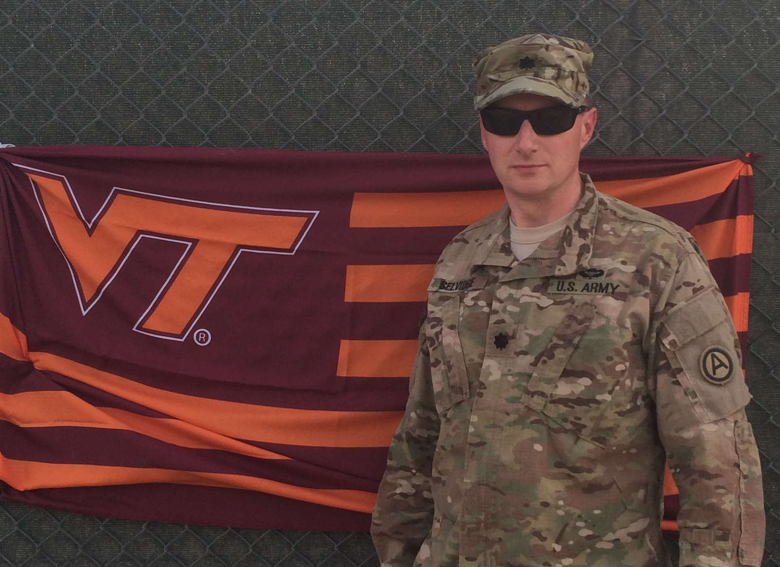 Lt. Col. Roy Selvidge, U.S. Army, Virginia Tech Corps of Cadets Class of 1993 standing in front of a VT flag.