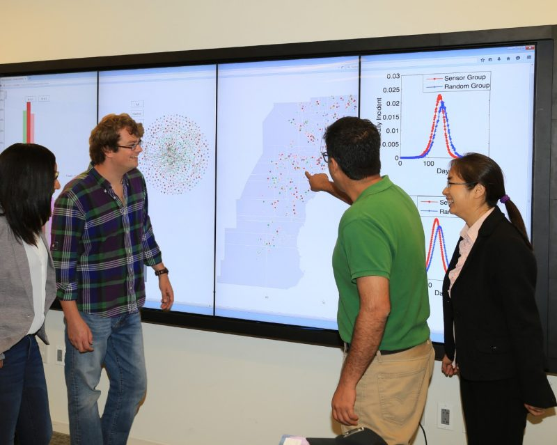 Four graduate students view a big data visualization.