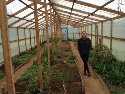 Travertine Orndorff checks out a greenhouse in Chile as part of her planning and research to build an educational garden for a school there.