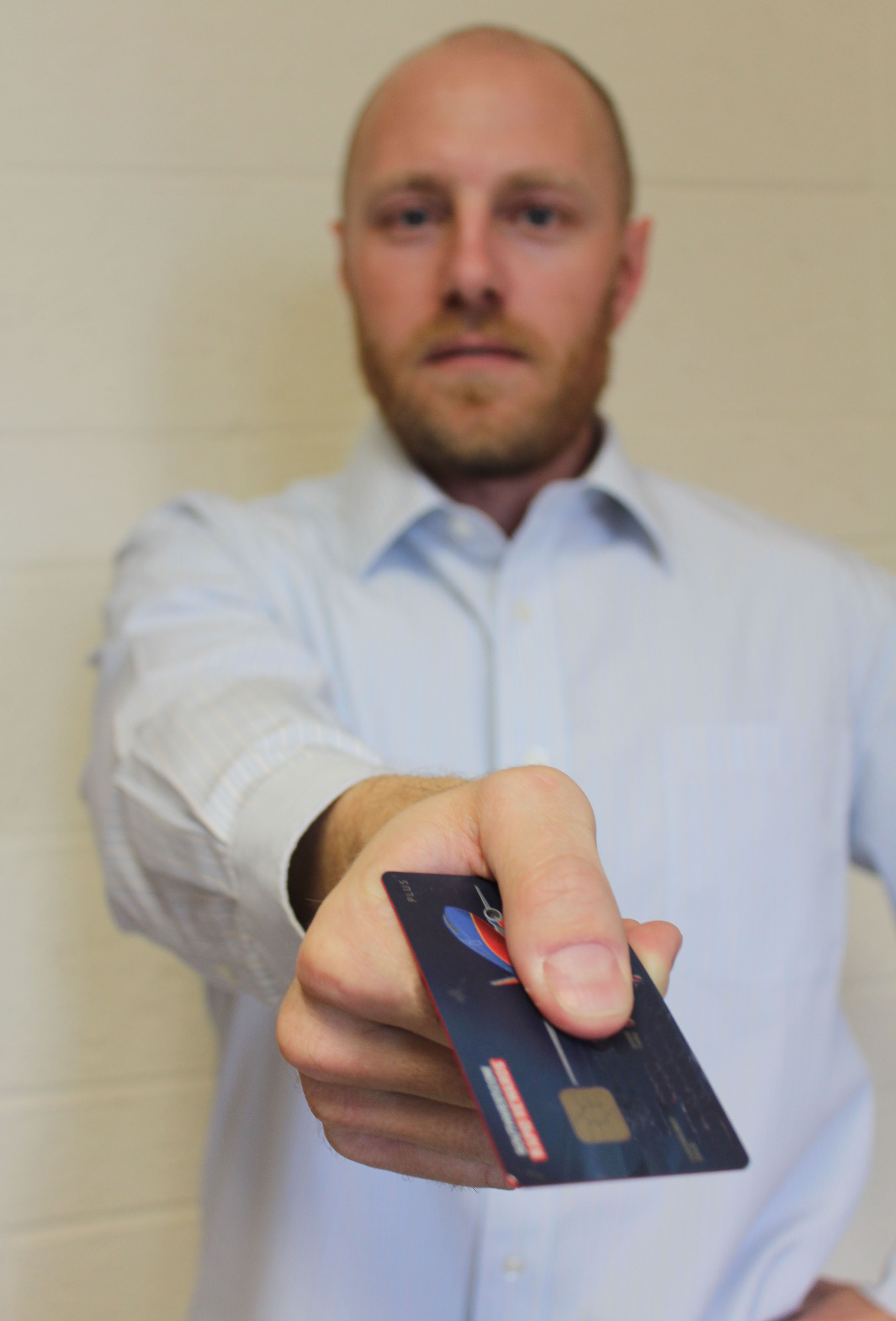 Man holds a credit card with a chip on it.