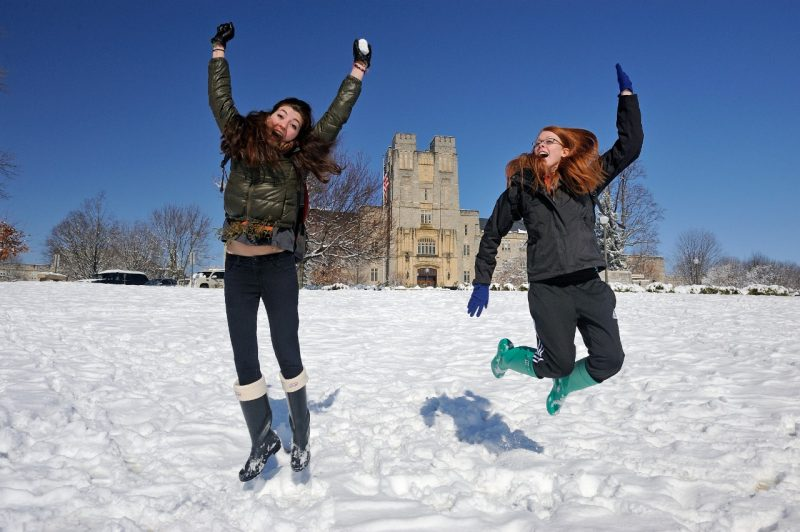 Students jumping in snow on the Drillfield