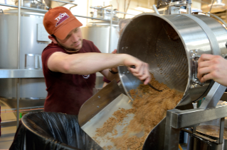A student spoons out spent barley from the brewhouse container into a trashcan. The professional-grade brewhouse is similar to what most craft beermaking facilities use, but optimized for teaching.