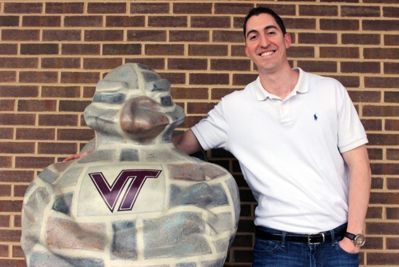 David Duckett stands with a statue of the HokieBird outside of his office.