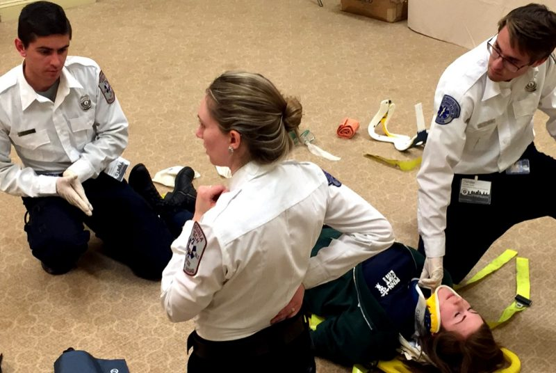 Three members of the ALS skills team attend to a patient.