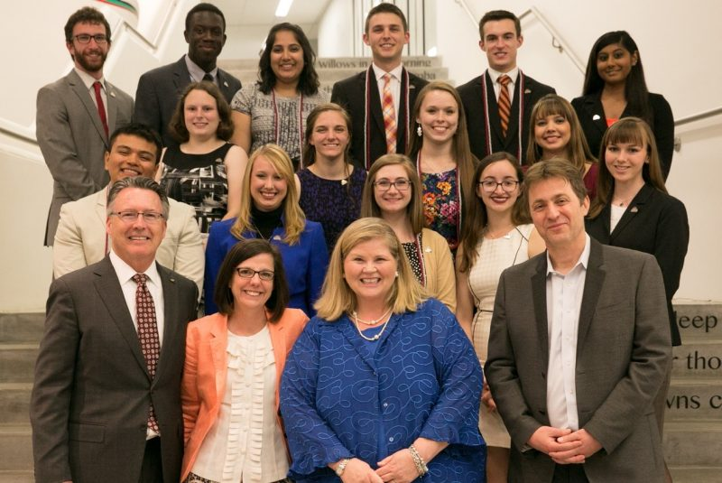President Tim Sands, Laura Sands, Vice President for Student Affairs Patty Perillo, and Executive Vice President and Provost Thanassis Rikakis pose with the inaugural cohort of 15 Keystone Fellows at the Moss Arts Center.