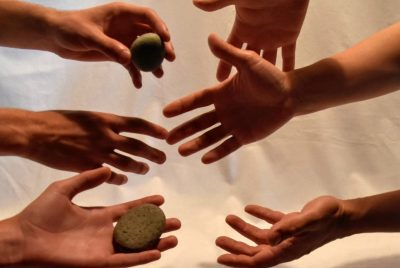 Hands holding and sharing stones
