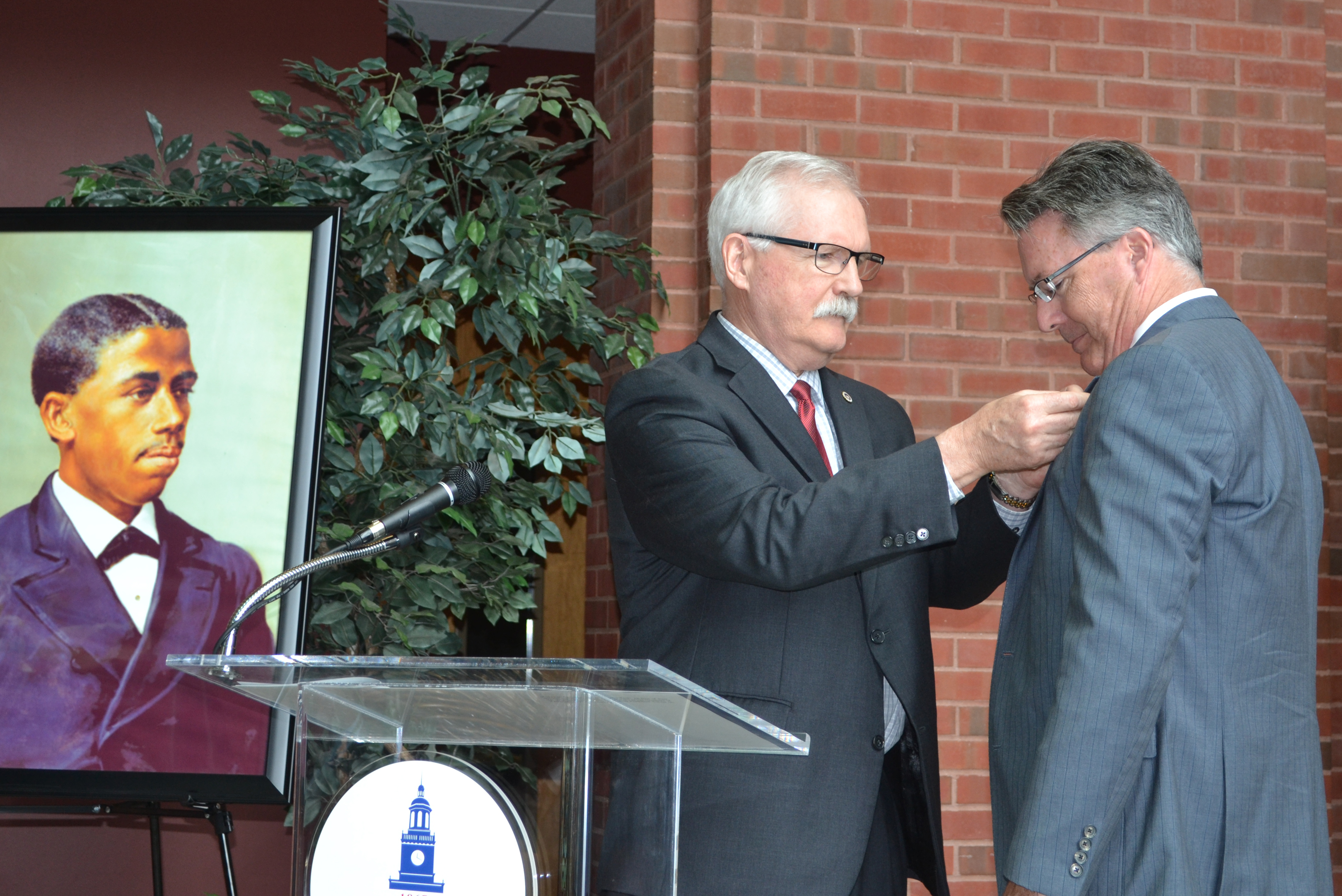 Howard University Associate Provost Gary L. Harris attaches a pin to President Tim Sands' lapel at the Bouchet Forum, where Sands received the Bouchet Legacy award