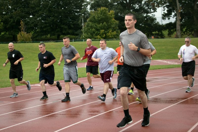 Ten members of the Virginia Tech Police Department run along a track in the rain.