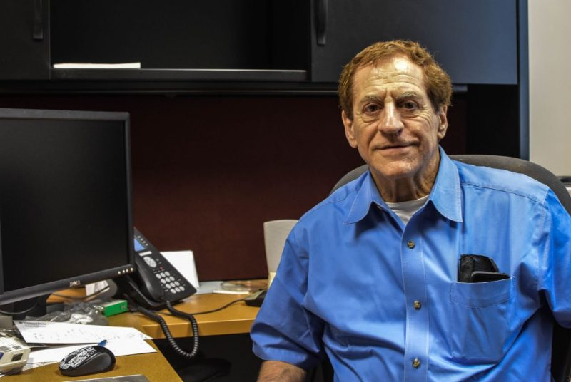 Richard Winett poses in a blue shirt at his office in 2017.