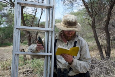 When David Millican, a doctoral candidate in biological sciences in the College of Sciences, goes out in the field, he always takes his four most trusty tools: a ladder, peeper camera, GPS device, and a journal for recording GPS candidates.  Photo by Jelena Djakovic.