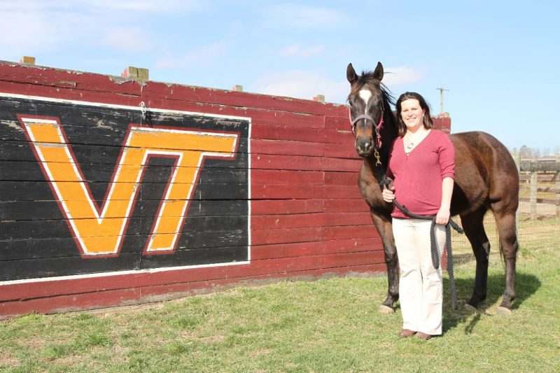 Joanna Kania poses with horse in front of VIrginia Tech sign