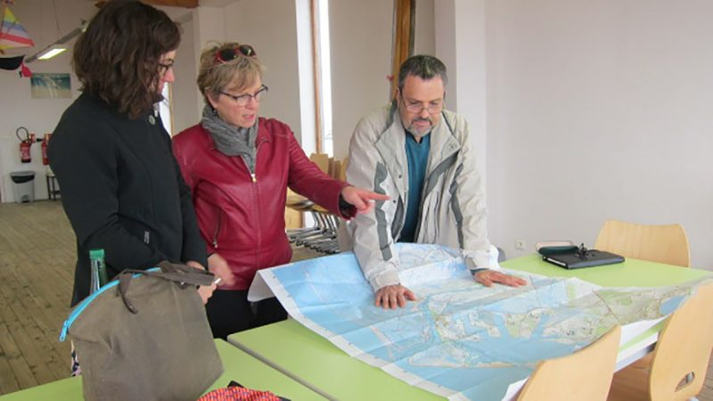 Left to right, Alison Cohen, Barbara Allen, and environmental activist  Gerard Casanova look over local map to plan health surveys in two French towns.