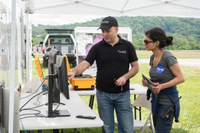 Amit Ganjoo, left, CEO of ANRA Technologies, and Arwa Aweiss, NASA's Unmanned Traffic Management National Campaign coordinator, watch as the flight paths of unmanned aircraft participating the tests appear on screens displaying a traffic-management software user interface.