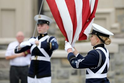 Members of the Corps of Cadets color guard lower the American flag.