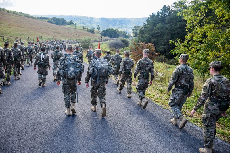 A long column of cadets walks down a rural roadway.
