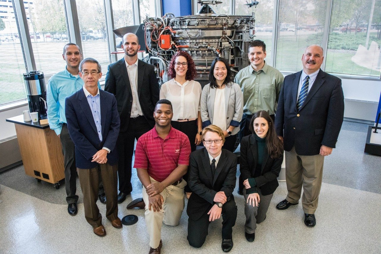The Virginia Tech students and advisors who work with Rolls-Royce as part of the company's University Technology Center program pose in front of an engine on the Rolls-Royce Indianapolis, Indiana, campus.