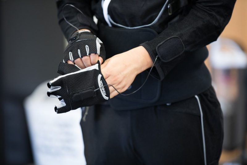 In the photo, a young man tries on a black cloth glove, which is connected to wires. It's a close up shot, focused only on the lower torso and the black suit.