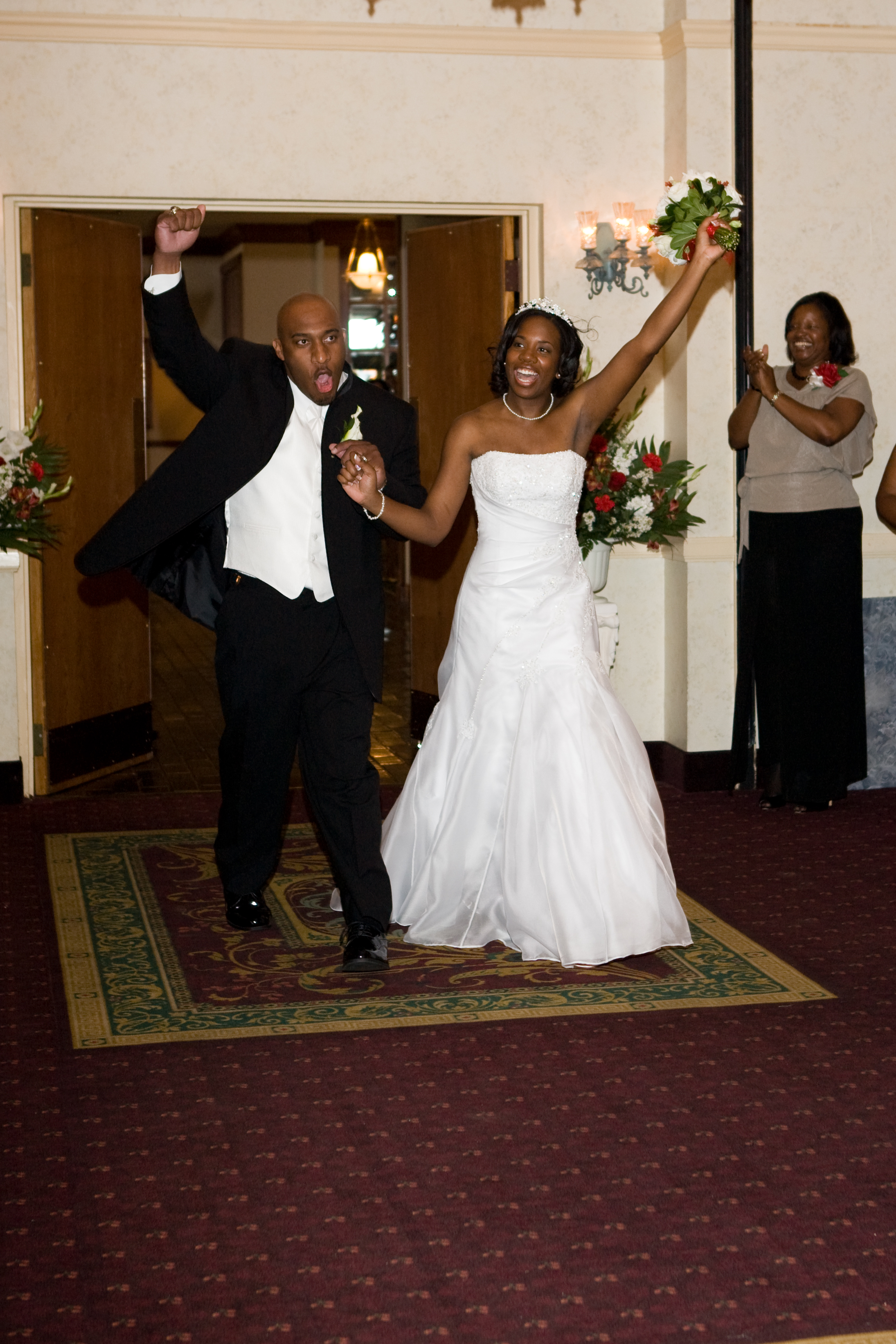 Image of the young couple walking into their reception holding hands and each raising an arm in a celebratory way.
