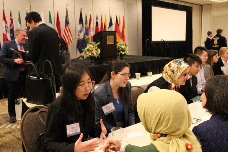 Students sit at table discussing trade issues with international trade representatives. Other conference attendees network in the background.