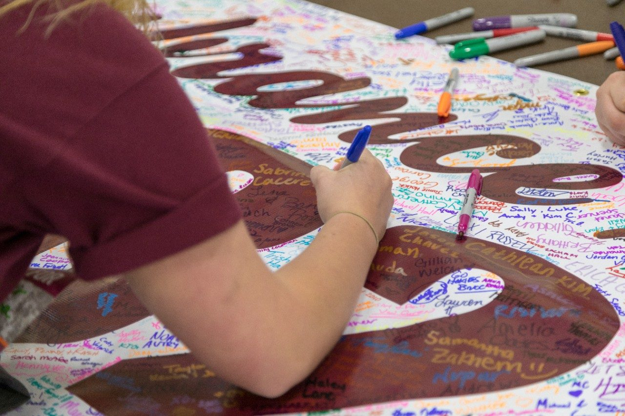 Participants sign the 2018 Run in Remembrance banner.