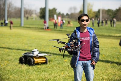 Electrical and computer engineering doctoral student Kevin Yu led a team that operated a coordinated pair of unmanned vehicles: the drone in this hands and the ground vehicle behind him.