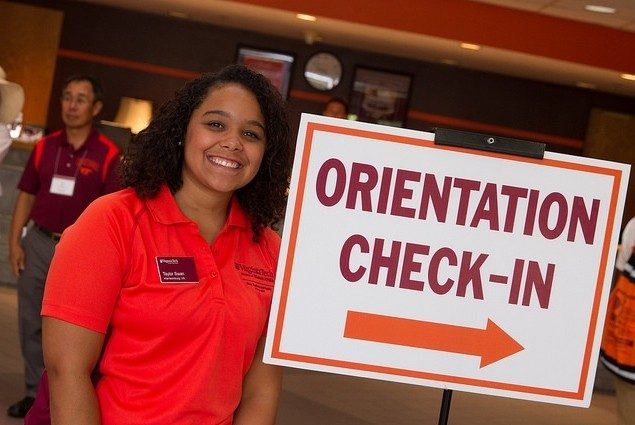 "Taylor Swan poses beside a sign that reads ""Orientation Check-In"" in Squires Student Center."