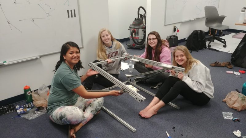 Four girls are sitting on the floor smiling as they hold up a metal device.