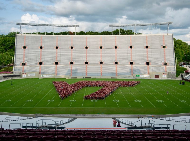 Photo of students in the shape of the VT athletic mark, in the middle of Lane Stadium