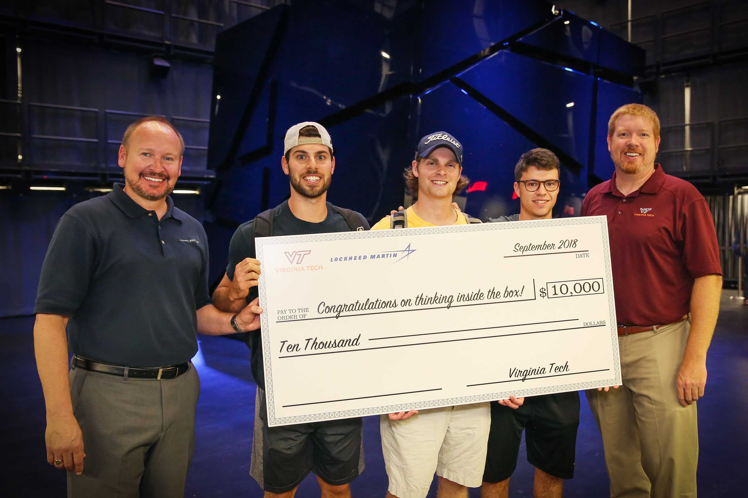 Three male, senior engineering students stand smiling holding a large check that says congratulations on thinking inside the box.