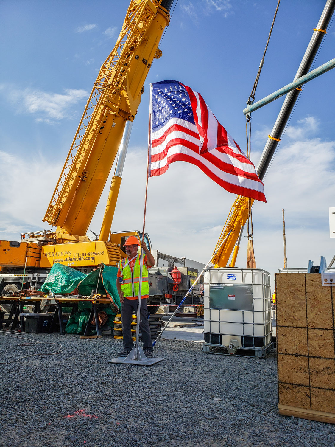 A man stands on gravel holding a flag pole with an American flag attached. Cranes stand behind him on an active construction site.