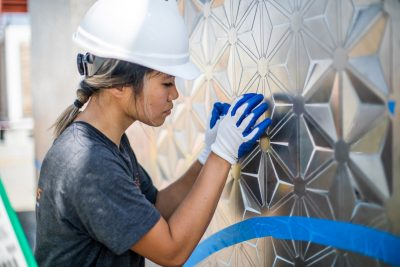 Michelle Le, a recently-graduated architecture student from Herndon, Virginia, presses in the screen wall's intricate pattern.