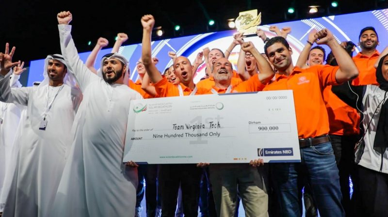 Photo of cheering team holding a check and a trophy.