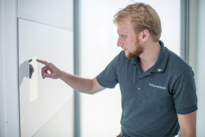 Electrical engineering student Matt Tucker of Knoxville, Tennessee, uses one of the home's touch screen panels to adjust settings in the house.