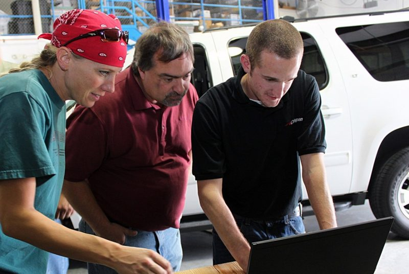 Researchers are training a student on how to conduct vehicle research installations in a garage at the Virginia Tech Transportation Institute.