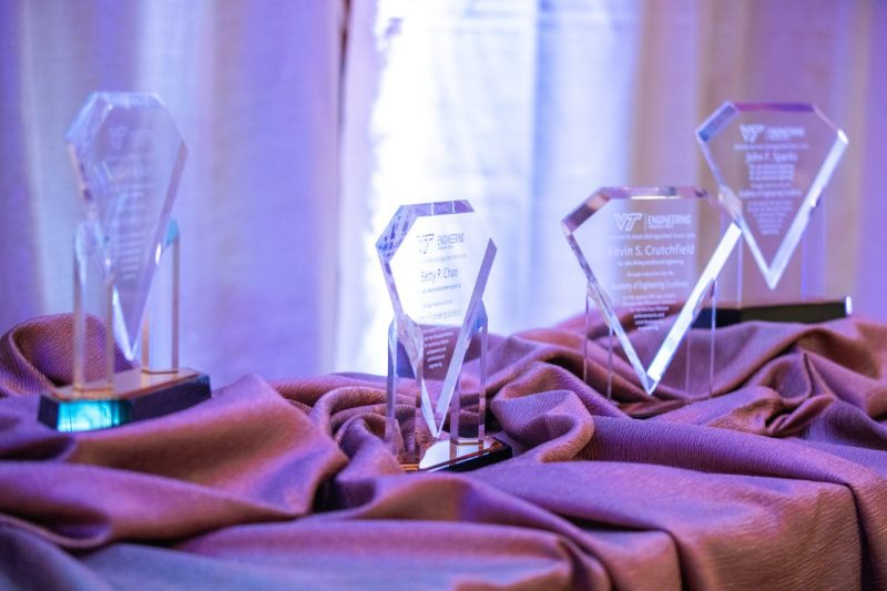 Four glass awards sit on a table covered by decorative tablecloths.