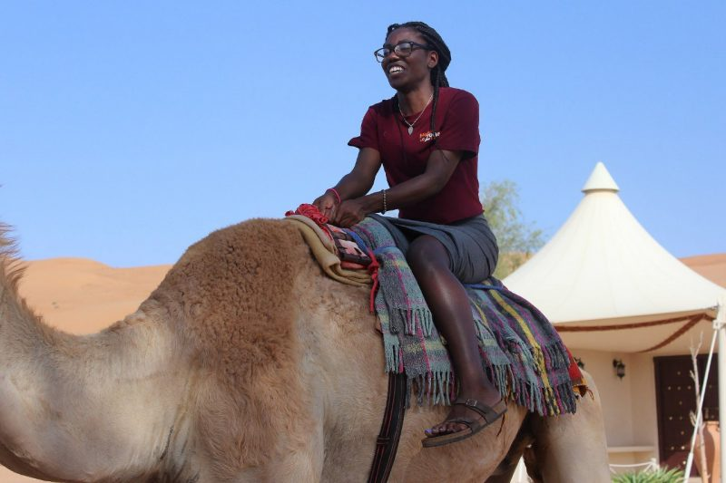 Katherine Louis rides a camel in Oman.