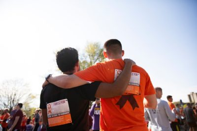 Two young men with runners bibs, stand arm in arm