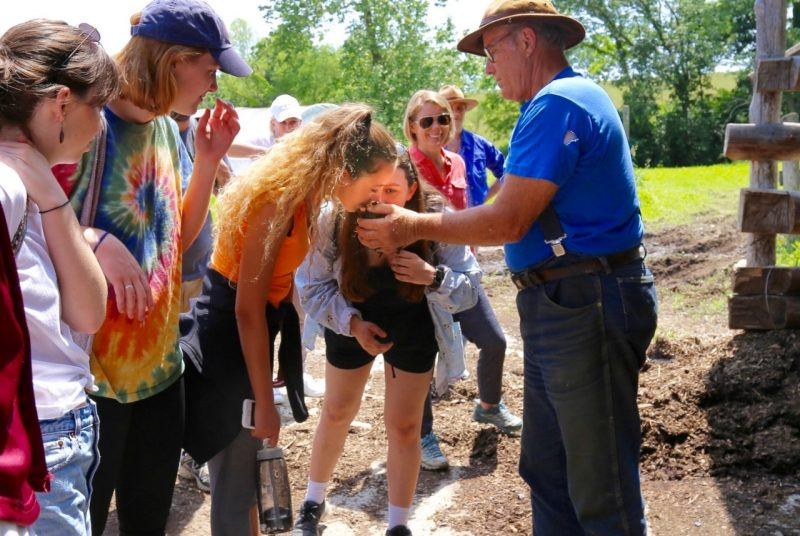 Rose Huenemann smells soil cupped in Joel Salatin's hand at Polyface Farms.