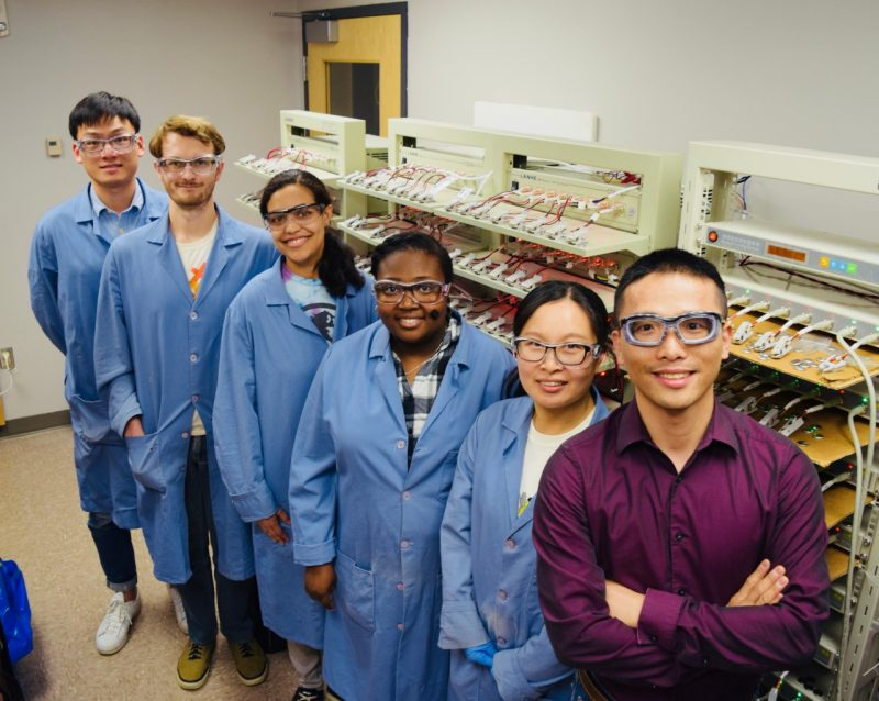 Five lab members and Feng Lin smile in the lab. The lab members wear blue lab coats and safety glasses, and Lin wears a red shirt.