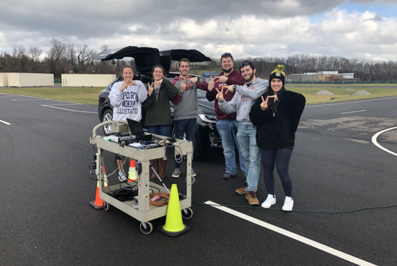 "Six engineering graduate students stand in front of a car and use their hands to make the ""VT"" shape."