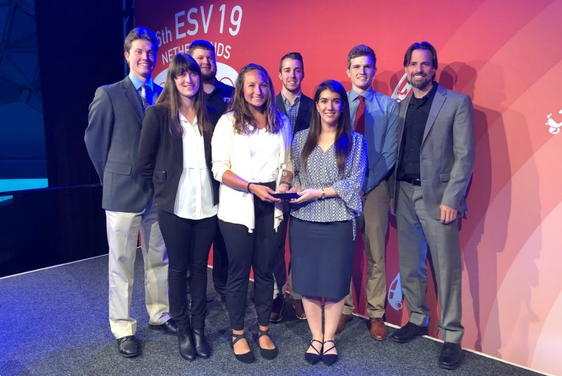 Seven students and their professor hold a glass trophy they received as the winners of the international 2019 Collegiate Student Safety Technology Design Competition.
