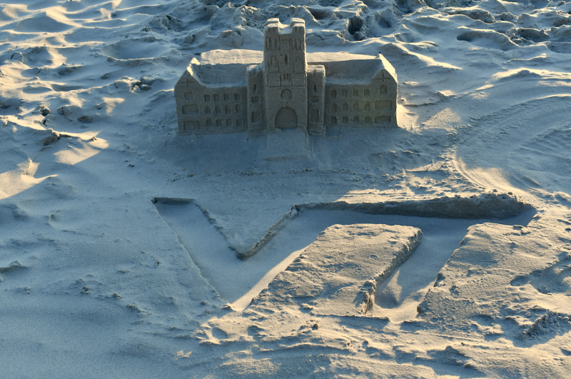 A sandcastle in the shape of Burruss Hall, sits behind the VT athletic mark, written in sand.